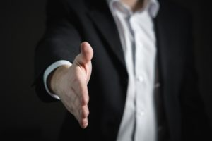 A businessman in a suit offering a handshake.