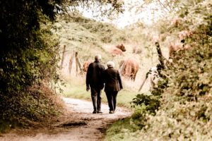 An elderly couple having a walk in the countryside after moving from Jersey City to a rural area.