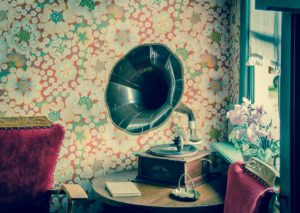 An old gramophone is placed on a wooden table in a corner of the room, near the window.